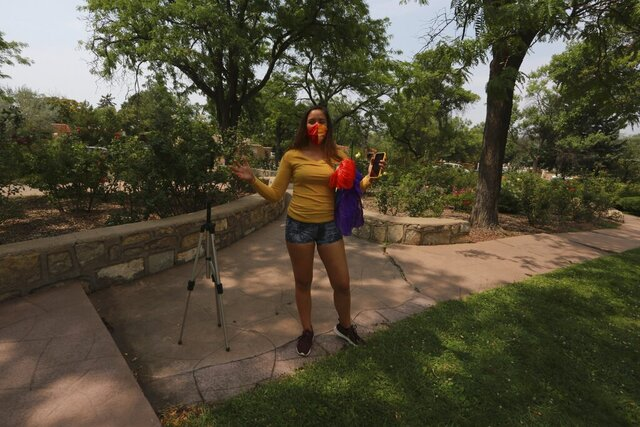 Tina Arons, 32, speaks as she removed her phone from a tripod at the Harvey Cornell Rose Park Monday, Aug. 24, 2020, in Santa Fe, New Mexico. Arons used the video recording setup to capture a dance routine with silk fan veils, draped over her shoulder, for and online she teaches. (AP Photo/Cedar Attanasio)