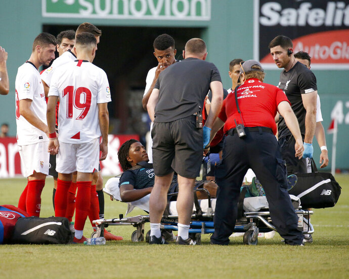 Sevilla players look on as Liverpool's Yasser Larouci is taken off the field on a stretcher after sustaining an injury during the second half of a friendly soccer match at Fenway Park, Sunday, July 21, 2019, in Boston. (AP Photo/Mary Schwalm)