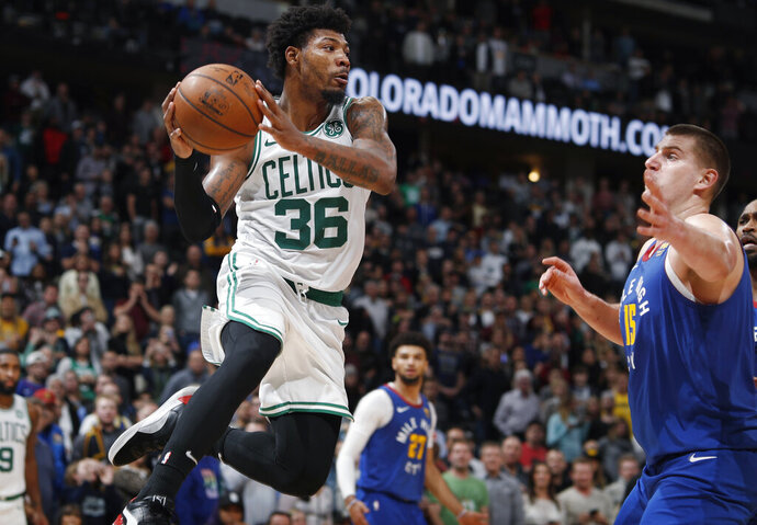 Boston Celtics guard Marcus Smart pulls in a rebound as Denver Nuggets center Nikola Jokic defends during the second half of an NBA basketball game Friday, Nov. 22, 2019, in Denver. The Nuggets won 96-92. (AP Photo/David Zalubowski)