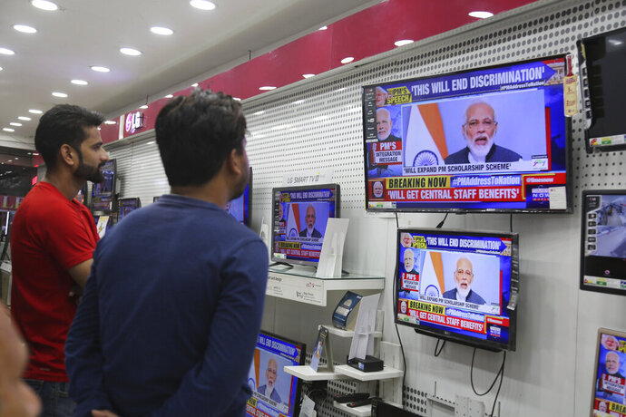 Indians watch Prime Minister Narendra Modi address the nation in a televised speech, in an electronics store in Jammu, India, Thursday, Aug. 8, 2019. Modi says a federally-ruled Indian portion of Kashmir will help end decades-old separatism incited by archrival Pakistan. Describing changes in Kashmir as historic, Modi assures Kashmiri people that the situation in the region will soon become normal. (AP Photo/Channi Anand)