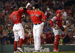 Boston Red Sox's J.D. Martinez, right, celebrates his two-run home run with Xander Bogaerts, next to Los Angeles Angels catcher Max Stassi during the fourth inning of a baseball game at Fenway Park, Friday, Aug. 9, 2019, in Boston. (AP Photo/Elise Amendola)