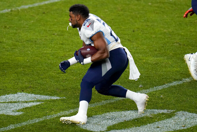 Tennessee Titans running back Jeremy McNichols (28) runs after losing his helmet during the second half of an NFL football game against the Denver Broncos, Monday, Sept. 14, 2020, in Denver. (AP Photo/Jack Dempsey)