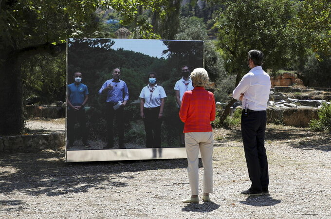 Greek Prime Minister Kyriakos Mitsotakis, right, and European Commission President Ursula von der Leyen, look at a big screen during an event at the Ancient Agora in Athens ,on Thursday, June 17, 2021. (Louiza Vradi/Pool via AP)