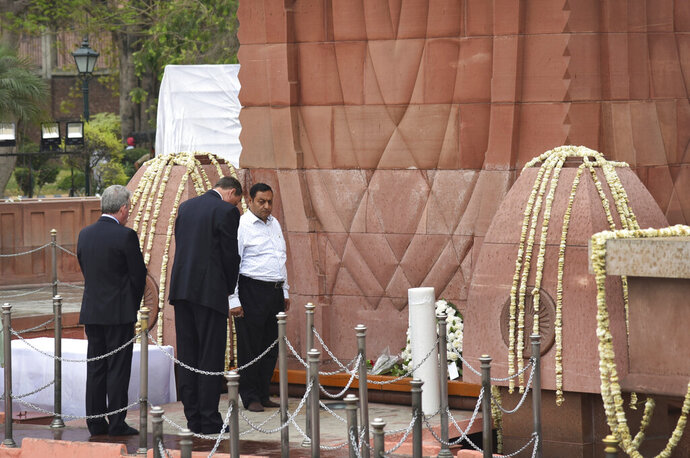 British High Commissioner to India Dominic Asquith, second left, pays homage to commemorate century of the Jallianwala Bagh incident, in Amritsar, India, Saturday, April 13, 2019. On April 13, 1919, hundreds were killed and more than 1,200 injured after British troops led by Reginald Dyer opened fire on a peaceful gathering at Jallianwala Bagh in Amritsar. (AP Photo/Prabhjot Gill)