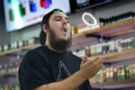 In this Tuesday, Sept. 3, 2019, photo, Devin Lambert, the manager at Good Guys Vape Shop, demonstrates to blow a vapor ring while using an e-cigarette in Biddeford, Maine. Efforts to ban flavored e-cigarettes and reduce their appeal to youngsters have sputtered under industry pressure in over a half-dozen states this year. The industry and its lobbyists urged lawmakers to leave mint and menthol alone. A proposed ban that President Donald Trump outlined Wednesday, Sept. 11, would supersede any state inaction and includes a ban on mint and menthol. (AP Photo/Robert F. Bukaty)