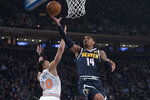 Denver Nuggets guard Gary Harris (14) goes to the basket past New York Knicks forward Kevin Knox (20) during the first half of an NBA basketball game Friday, March 22, 2019, at Madison Square Garden in New York. (AP Photo/Mary Altaffer)