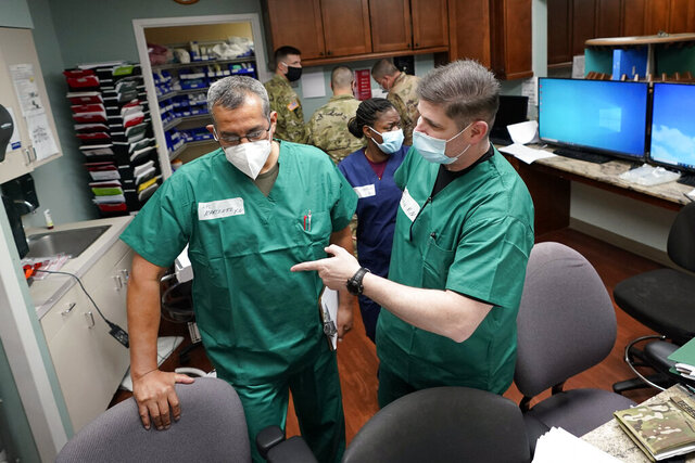 FILE - In this July 16, 2020 file photo, Registered nurses Army Lt. Col. Oswaldo Martinez, left, and Maj. Andrew Wieher, right, with the Urban Augmentation Medical Task Force, work to setup a nurses station inside a wing at United Memorial Medical Center, in Houston.  Texas reported a new daily record for virus deaths Friday and more than 10,000 confirmed cases for the fourth consecutive day. (AP Photo/David J. Phillip)