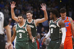 Milwaukee Bucks guard George Hill (3), center Brook Lopez, center, and guard Wesley Matthews (9) celebrate in front of Oklahoma City Thunder forward Danilo Gallinari, right, late in the second half of an NBA basketball game Sunday, Nov. 10, 2019, in Oklahoma City. (AP Photo/Sue Ogrocki)