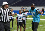 NFL player Mario Addison of the Carolina Panthers complains to the referee as he coaches a young team during the final tournament for the UK's NFL Flag Championship, featuring qualifying teams from around the country, at the Tottenham Hotspur Stadium in London, Wednesday, July 3, 2019. The new stadium will host its first two NFL London Games later this year when the Chicago Bears face the Oakland Raiders and the Carolina Panthers take on the Tampa Bay Buccaneers. (AP Photo/Frank Augstein)