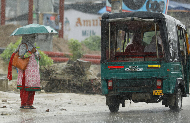 A woman with her face covered stands in the rain in Prayagraj, India, Wednesday, July 29, 2020. India is the third hardest-hit country by the pandemic in the world after the United States and Brazil. (AP Photo/Rajesh Kumar Singh)
