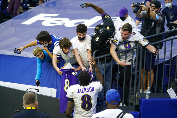Fans try for photos and autographed as Baltimore Ravens quarterback Lamar Jackson (8) leaves the field following an NFL football game against the Indianapolis Colts in Indianapolis, Sunday, Nov. 8, 2020. The Ravens defeated the Colts 24-10. (AP Photo/Darron Cummings)