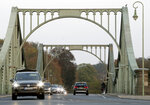 In this Wednesday, Oct. 23, 2019 photo cars drive on the 'Glieniker Bruecke' (Glienicke Bridge) in Potsdam, Germany. During the Cold War, the Glienicke Bridge connecting West Berlin to Potsdam in East Germany was famously used as a site for exchanging captured foreign agents. Since the two opposing sides couldn't agree to work together when the bridge required repairs, each conducted them separately. The paint was applied differently and faded un-uniformly, and the two shades of green meeting at the middle of the bridge are still clearly visible today. (AP Photo/Michael Sohn)