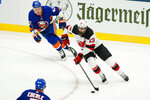 New Jersey Devils' Nico Hischier (13) drives past New York Islanders' Leo Komarov (47) and Jordan Eberle during the first period of an NHL hockey game Saturday, May 8, 2021, in Uniondale, N.Y. (AP Photo/Frank Franklin II)