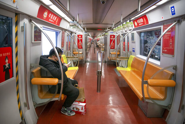 In this Sunday, Jan. 26, 2020 photo, a man wearing a face mask rides in a nearly empty subway train in Beijing. Fears of a virus outbreak have kept many indoors and at home in China's capital. Cultural landmarks such as the Great Wall and Forbidden City have closed their doors to visitors, nearly deserted shopping malls have reduced their operating hours, and restaurants that remain open draw just a handful of customers. (AP Photo/Mark Schiefelbein)