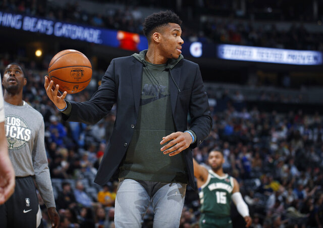 Milwaukee Bucks forward Giannis Antetokounmpo fields the ball as he shoots with teammates as they warm up for the second half of an NBA basketball game against the Denver Nuggets, Monday, March 9, 2020, in Denver. The Nuggets won 109-95. (AP Photo/David Zalubowski)