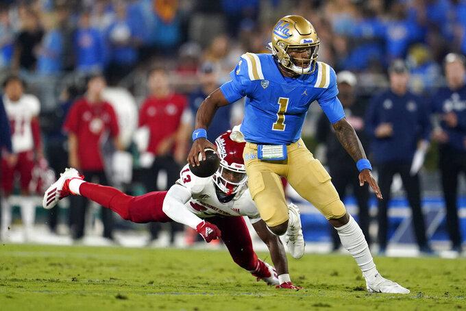 UCLA quarterback Dorian Thompson-Robinson (1) runs past Fresno State defensive back Justin Houston (13) during the first half of an NCAA college football game Saturday, Sept. 18, 2021, in Pasadena, Calif. (AP Photo/Marcio Jose Sanchez)