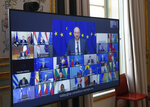 FILE - In this March 25, 2021, file photo, European Council President Charles Michel shown on a screen, center, speaks during a video conference of a EU summit projected at the Elysee Palace in Paris. European Union leaders no longer meet around a common oval summit table to broker their famed compromises. Instead, each of the 27 watches the others with suspicion via a video screen that shows a mosaic of faraway capitals. (AP Photo/Michel Euler, Pool, File)