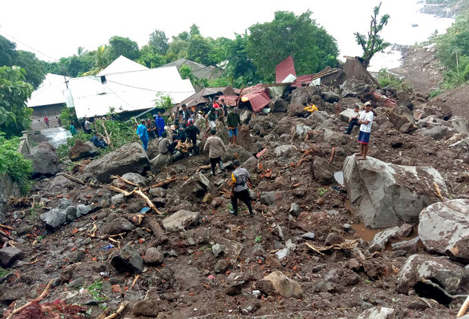 Rescuers search for victims at a village hit by a landslide in Ile Ape Timur on Lembata Island, East Nusa Tenggara province, Indonesia, Monday, April 5, 2021. Multiple disasters caused by torrential rains in eastern Indonesia and neighboring East Timor have left a number of people dead or missing as rescuers were hampered by damaged bridges and roads and a lack of heavy equipment Monday. (AP Photo/Ricko Wawo)