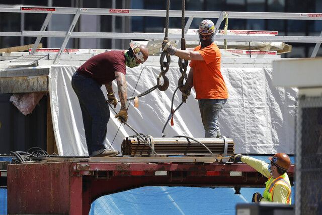 Workers prepare to hoist metal materials at a construction site in Boston's Seaport District, Tuesday, May 19, 2020. In the first phase of reopening outlined by Mass. Gov. Charlie Baker, that began Monday, May 18th, construction is included among industries that can reopen provided they follow standards meant to curb the spread of the coronavirus. (AP Photo/Steven Senne)