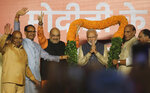 Bharatiya Janata Party (BJP) President Amit Shah, third left, Home Minister Rajnath Singh, second right, and other party leaders present a giant floral garland to Indian Prime Minister Narendra Modi at the party headquarters in New Delhi, India, Thursday, May 23, 2019. Indian Prime Minister Narendra Modi's party claimed it had won reelection with a commanding lead in Thursday's vote count, while the stock market soared in anticipation of another five-year term for the pro-business Hindu nationalist leader. (AP Photo/Manish Swarup)