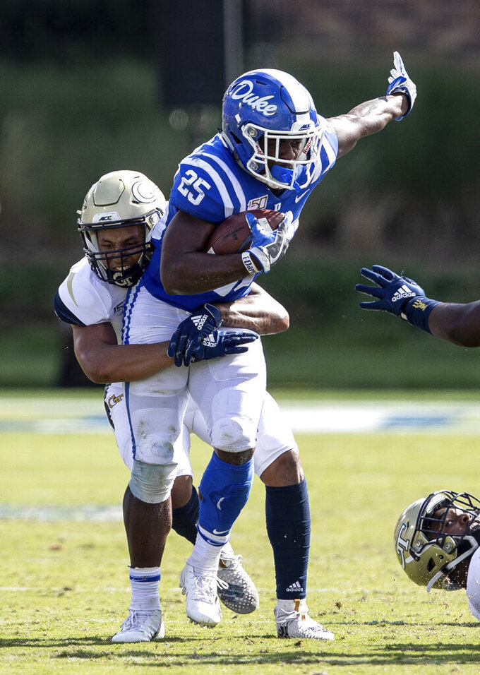Duke's Deon Jackson (25) carries the ball as Georgia Tech's Avery Showell (13) attempts a tackle during an NCAA college football game in Durham, N.C., Saturday, Oct. 12, 2019. (AP Photo/Ben McKeown)