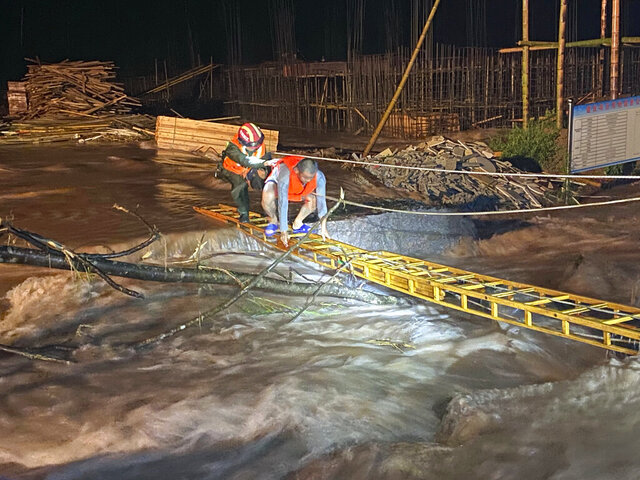 A rescuer helps a worker cross a ladder to get across floodwaters from a construction site in Jing'an county in central China's Jiangxi province midnight Friday, July 3, 2020. A wide swath of southern China braced Sunday for more seasonal rains and flooding. (Chinatopix via AP)