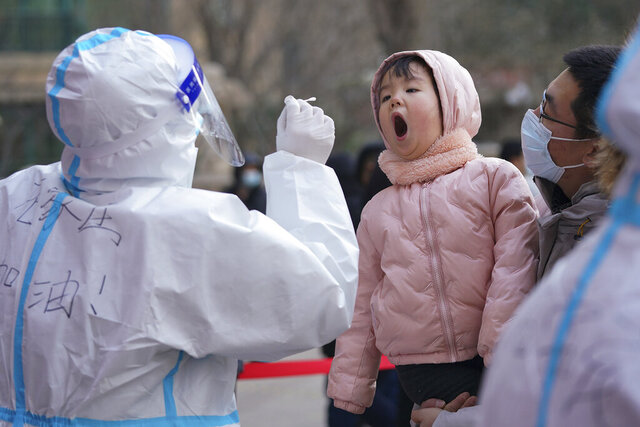 In this photo released by Xinhua News Agency, a medical staff in a protective suit prepares to take a swab from a child near a residential area in Shijiazhuang in north China's Hebei province on Wednesday, Jan. 6, 2021. Lockdown measures were being imposed in a northern Chinese province where coronavirus cases more than doubled in the region near Beijing that's due to host some events in next year's Winter Olympics. (Mu Yu/Xinhua via AP)