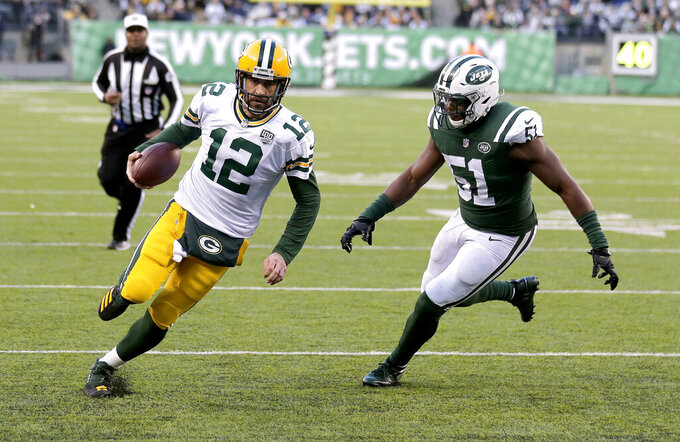 FILE - In this Dec. 23, 2018, file photo, Green Bay Packers quarterback Aaron Rodgers runs for a touchdown as New York Jets outside linebacker Brandon Copeland (51) chases him during the second half of an NFL football game in East Rutherford, N.J. Copeland is suing a company that sold a supplement he says was contaminated with a banned substance that didn't appear on the product's label. Copeland practiced Wednesday, Oct. 9, 2019, for the first time this season after being suspended by the NFL for the first four regular-season games for violating the league's policy on performance-enhancing drugs. Copeland says he failed the test on April 15, and the NFL announced his suspension on Aug. 21. (AP Photo/Seth Wenig, File)