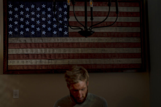 Brad Snyder sits in his kitchen decorated with a flag handcrafted by Brooklyn firefighters using recycled firehose, at his home in Princeton, N.J., on Wednesday, Aug. 4, 2021. Snyder, who discovered a love for the classroom after teaching ethics a few years ago at the Naval Academy, started a Ph.D. at Princeton in 2020. He's focusing on relationships between militaries and the people they serve. (AP Photo/Emilio Morenatti)