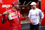 Ferrari driver Sebastian Vettel of Germany, left, speaks with Mercedes driver Valtteri Bottas of Finland outside his team garage after qualification ahead of the Belgian Formula One at Spa-Francorchamps, Belgium, Saturday, Aug. 31, 2019. The Belgian Formula One race will take place on Sunday. (AP Photo/Francisco Seco)