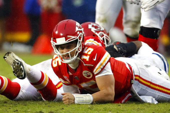 Kansas City Chiefs quarterback Patrick Mahomes (15) grimaces after his leg is caught by Indianapolis Colts defensive tackle Denico Autry, rear, during the first half of an NFL divisional football playoff game in Kansas City, Mo., Saturday, Jan. 12, 2019. (AP Photo/Charlie Riedel)