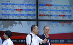 Men stand in front of an electronic stock board showing Japan's Nikkei 225 index at a securities firm in Tokyo Friday, Aug. 10, 2018. Shares were lower in Asia on Friday, tracking losses on Wall Street, despite the release of data showing Japan's economy resumed its longtime expansion in the last quarter. (AP Photo/Eugene Hoshiko)