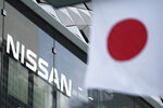 In this May 10, 2019, photo, Nissan logo is seen near a Japanese flag at the automaker's showroom in Tokyo. Nissan filed a civil suit Wednesday, Feb. 12, 2020 seeking 10 billion yen ($91 million) in damages from the Japanese automaker's former Chairman Carlos Ghosn. (AP Photo/Eugene Hoshiko)