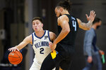 Villanova's Collin Gillespie, left, tries to get past Marquette's Theo John during the second half of an NCAA college basketball game, Wednesday, Feb. 10, 2021, in Villanova, Pa. (AP Photo/Matt Slocum)