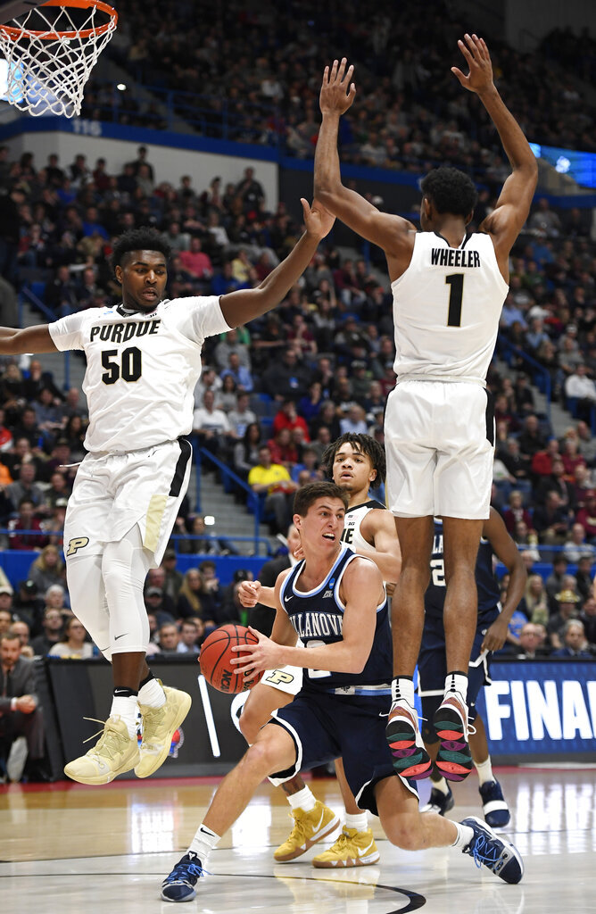 Villanova's Collin Gillespie (2) looks to pass around the defense of Purdue's Trevion Williams (50) and Aaron Wheeler (1) during the first half of a second round men's college basketball game in the NCAA tournament, Saturday, March 23, 2019, in Hartford, Conn. (AP Photo/Jessica Hill)