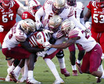 North Carolina State's Matthew Alderfer (35) is tackled by Florida State's Hamsah Nasirildeen (23), Fredrick Jones (55) and Jaiden Woodbey (20) during the first half of an NCAA college football game in Raleigh, N.C., Saturday, Nov. 3, 2018. (AP Photo/Chris Seward)