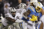 Los Angeles Chargers running back Melvin Gordon, right, carries as Oakland Raiders defensive end Clelin Ferrell (96) reaches for him during the first half of an NFL football game in Oakland, Calif., Thursday, Nov. 7, 2019. (AP Photo/Ben Margot)