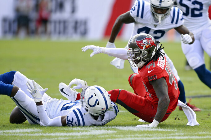 Tampa Bay Buccaneers running back Dare Ogunbowale (44) fumbles the football after getting hit by Indianapolis Colts defensive back George Odum (30) during the first half of an NFL football game Sunday, Dec. 8, 2019, in Tampa, Fla. (AP Photo/Jason Behnken)