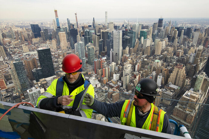 FILE - In this March 8, 2019, file photo, work continues on an outdoor observation deck on the 30 Hudson Yards office building in New York. Business economists expect U.S. economic growth to slow this year and next, but they say the economy will avoid recession. (AP Photo/Mark Lennihan, File)