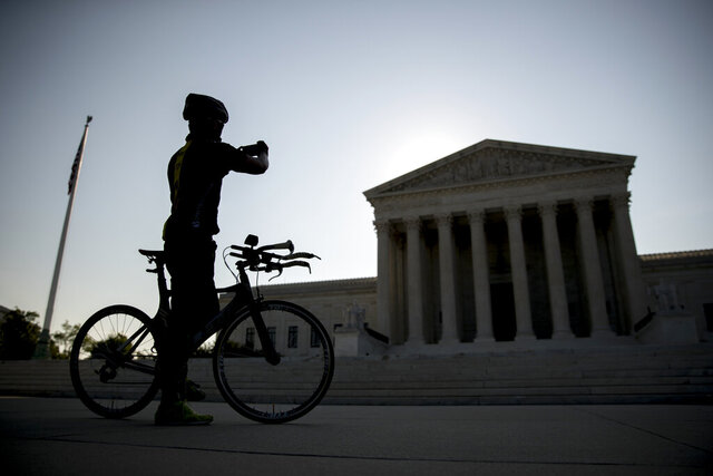 A man on a bicycle stops to take a photograph outside the Supreme Court, Wednesday, July 8, 2020, in Washington. (AP Photo/Andrew Harnik)