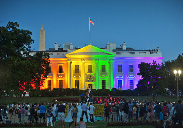 FILE - In this Friday, June 26, 2015 file photo, people gather in Lafayette Park to see the White House illuminated with rainbow colors in commemoration of the Supreme Court's ruling to legalize same-sex marriage in Washington. The Trump administration Friday, June 12, 2020, finalized a regulation that overturns Obama-era protections for transgender people against sex discrimination in health care. (AP Photo/Pablo Martinez Monsivais, File)