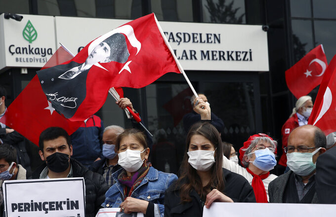 People wearing masks to help protect against the spread of coronavirus, attend a protest outside the US embassy, in Ankara, Turkey, Monday, April 26, 2021. Turkey's President Recep Tayyip Erdogan has announced the country's strictest pandemic restrictions so far, closing businesses and schools and limiting travel for nearly three weeks starting Thursday to fight a surge in COVID-19 infections and deaths. (AP Photo/Burhan Ozbilici)