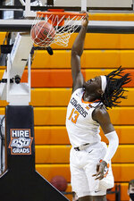 Oklahoma State guard Isaac Likekele (13) dunks in the first half of an NCAA college basketball game against West Virginia, Monday, Jan. 4, 2021, in Stillwater, Okla. (AP Photo/Sue Ogrocki)