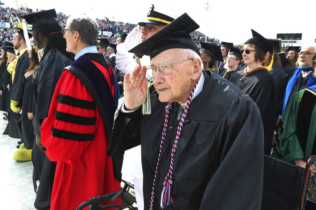 FILE - In this May 5, 2018, file photo, World War II veteran Bob Barger salutes during the national anthem at the commencement ceremony at the University of Toledo, in Toledo, Ohio. Barger, a World War II veteran from Ohio who received his college degree last spring nearly 70 years after he last sat in a classroom, died Wednesday, Jan. 9, 2019, Newcomer Funeral Home in Toledo said. He was 97. (AP Photo/Carlos Osorio, File)