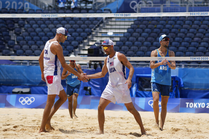 Philip Dalhausser, left, of the United States, celebrates with teammate Nicholas Lucena, during a men's beach volleyball match against Argentina at the 2020 Summer Olympics, Thursday, July 29, 2021, in Tokyo, Japan. (AP Photo/Petros Giannakouris)