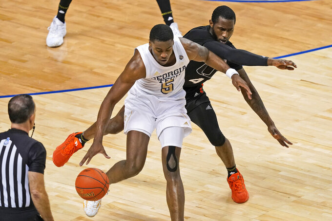 Georgia Tech forward Moses Wright (5) keeps the ball from Miami guard Elijah Olaniyi (4) during the second half of an NCAA college basketball game in the quarterfinal round of the Atlantic Coast Conference tournament in Greensboro, N.C., Thursday, March 11, 2021. (AP Photo/Gerry Broome)