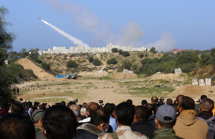 Palestinian militants watch a rocket fired during a military drill organized by military factions outside Gaza City, Tuesday, Dec. 29, 2020. Palestinian militants in the Gaza Strip fired a salvo of rockets into the Mediterranean Sea on Tuesday as part of a self-styled military drill aimed at preparing for a possible war with Israel. (AP Photo/Adel Hana)