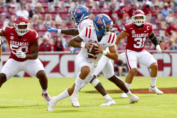 Mississippi quarterback Matt Corral (2) scrambles out of the pocket against Arkansas during the first half of an NCAA college football game Saturday, Oct. 17, 2020, in Fayetteville, Ark. (AP Photo/Michael Woods)