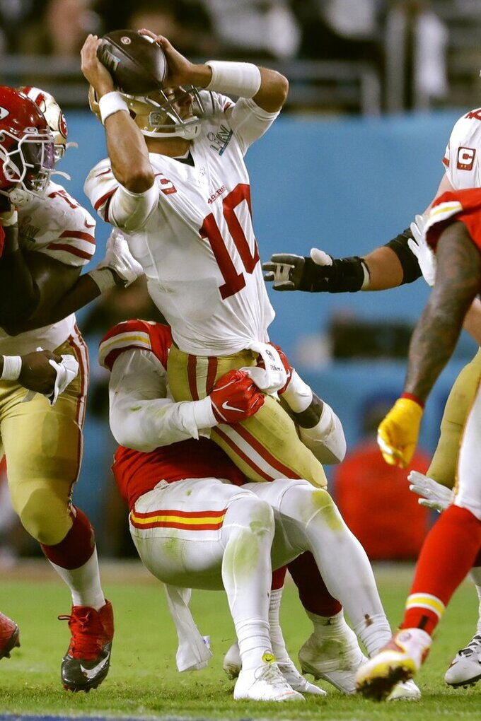 Kansas City Chiefs' Frank Clark, left, tries to tackle San Francisco 49ers' quarterback Jimmy Garoppolo during the second half of the NFL Super Bowl 54 football game Sunday, Feb. 2, 2020, in Miami Gardens, Fla. (AP Photo/John Bazemore)