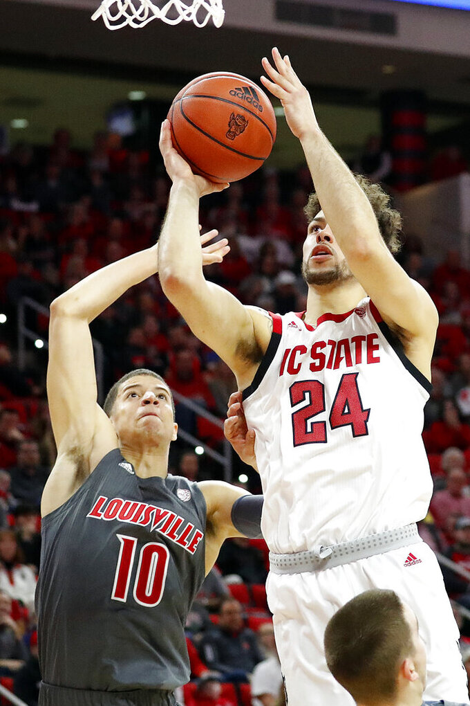 North Carolina State's Devon Daniels (24) drives the ball past Louisville's Samuell Williamson (10) during the first half of an NCAA college basketball game in Raleigh, N.C., Saturday, Feb. 1, 2020. (AP Photo/Karl B DeBlaker)